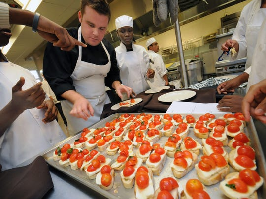 In this 2011 photo, Instructor and Executive Chef of Culinary Arts program at William Penn High School Kip Poole helps out his students serve crostini.