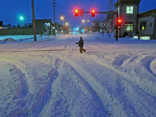 Madori Griffin, who says her car was snowed in, makes her way through an intersection while walking to work in the intensive care unit of Sanford Hospital early Monday, Dec. 26, 2016, in Bismarck, N.D. The combination of freezing rain, snow and high winds that forced the shutdown Sunday of vast stretches of highways in the Dakotas continued into Monday morning, and authorities issued no-travel warnings for much of North Dakota.