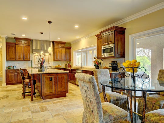 The gourmet kitchen has dark wood cabinetry, stainless appliances, travertine backsplash, granite countertops and a huge island with sink.