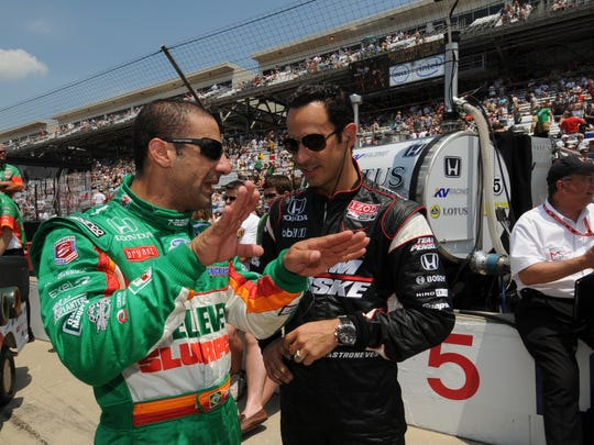 FILE – Tony Kanaan and Helio Castroneves compare notes