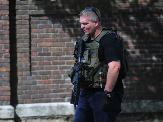 Officer Austin Lipps wears some SWAT gear and carries his rifle back to his vehicle Friday after Jonathan McClellan was captured.