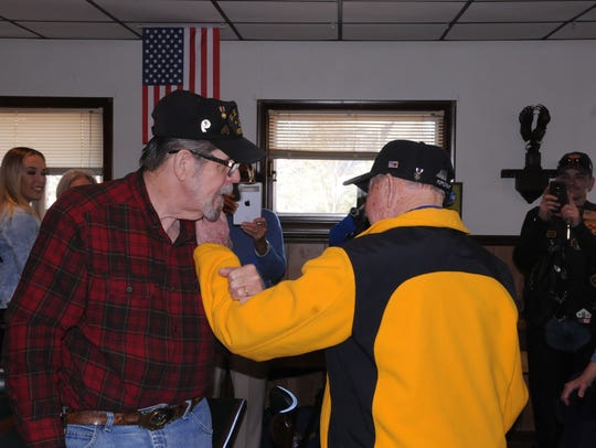 Bayard Horn, right, shakes the hand of fellow veteran