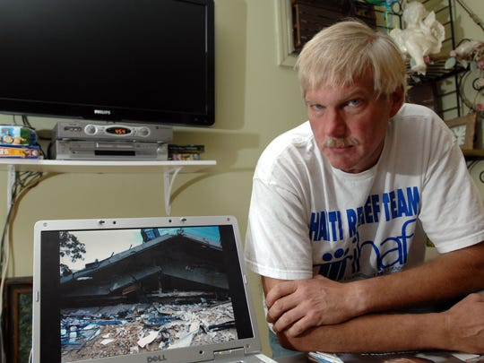 In this January 2010 photo, Andrew Topp had just returned from Les Cayes, Haiti where he was building housing for locals. Picture on computer of earthquake damage.