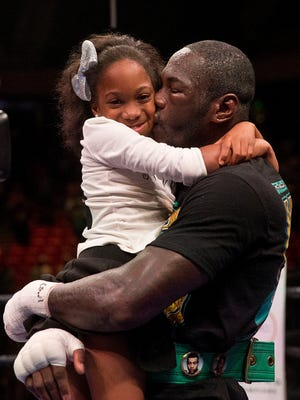 Deontay Wilder, kisses his daughter Naieya Wilder, 10, after he defeated Johann Duhaupas in the 11th round during a WBC heavyweight title boxing match, Saturday, Sept. 26, 2015, in Birmingham, Ala. Wilder took up boxing to support his daughter, who was born with spina bifida.