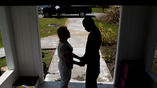 Michelle-Ruth Haskins, of Naples, prays with Daniel