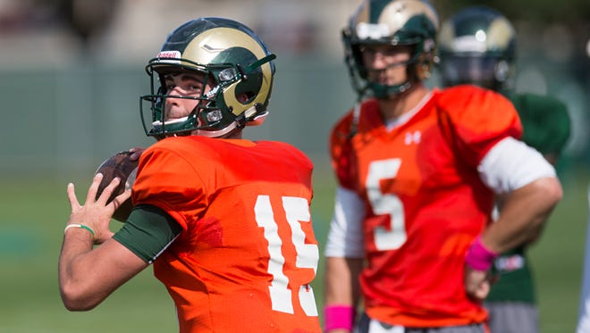 Collin Hill, a true freshman, throws a pass during CSU's football practice Wednesday as fellow quarterback Faton Bauta looks on. Hill and Bauta are in a three-man race with returning starter Nick Stevens for the starting job.