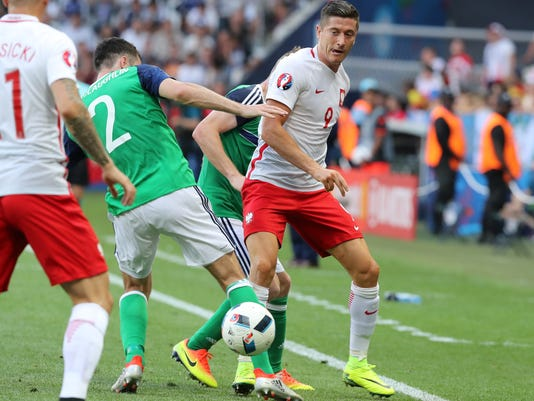 Poland's Robert Lewandowski, right, passes the ball to Poland's Kamil Grosicki, left, during the Euro 2016 Group C soccer match between Poland and Northern Ireland at the Allianz Riviera stadium in Nice, France, Sunday, June 12, 2016. (AP Photo/Thanassis Stavrakis)