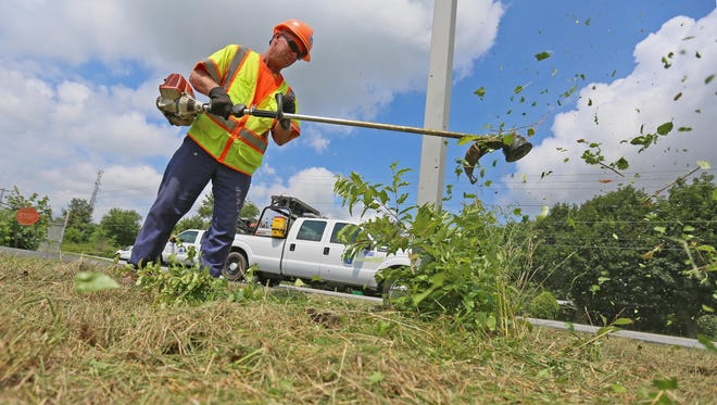 Randy Crisco, an operator for Del Dot in Cheswold, trims grass with a weed eater along McGee Road.