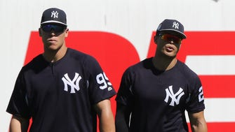 Aaron Judge and Giancarlo Stanton, both in left field waiting a fly ball during practice.