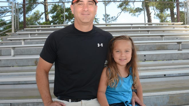 Elizabeth coach Rhon Morgan poses for a photo with his daughter, Caroline. Morgan led the Bulldogs to the Class C state championship, the school's first baseball title in 14 years.