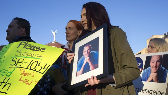 Supporters hold signs on Jan. 26, 2017, at the Arizona Capitol in Phoenix, before a hearing on a bill in honor of Joe Smith, a Phoenix teen killed in a semi crash. Supporters include Gabrielle Bell (second from right), who was Joe's girlfriend.