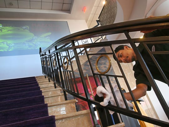 Marquinn Taylor, Public Space Attendee, cleans the grand staircase at the Main Street entrance at the Hyatt Regency Rochester at 125 East Main Street in downtown Rochester Thursday, Oct. 6, 2016.