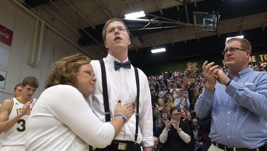 Josh Speidel gets a hug from his mother Lisa as his father Dave looks on before being introduced prior to the start of the University of Vermont's game against Stony Brook in Burlington on Saturday.