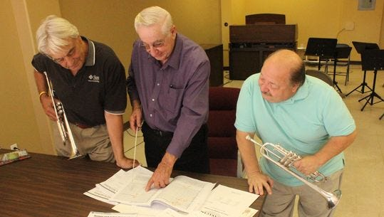 SNSO members, from left, Jan Sando, Selmer Spitzer and Rick Boniface prepared for the group's performance in November.
