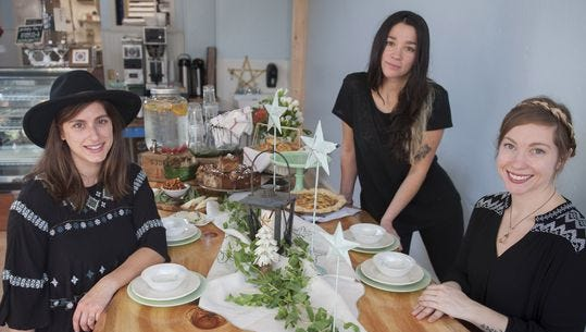 Maura Rosato (from left), Valentina Fortuna and Lindsey Ferguson gather around the communal table at Constellation Collective. The Collingswood cafe and bakery is celebrating its first year in business.