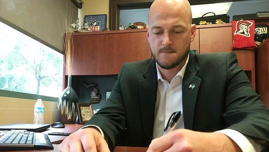 """Former Michigan State QB Ryan Van Dyke sits at his desk in Northville, drawing up the game-winning play in 2001 against Notre Dame. The play was called """"93-X-Cross."""""""