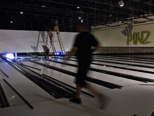 Workers team up during a lighting installation at the VIP section of the newly built HeadPinz Fort Myers on June 24. The entertainment center is expected to open July 16.