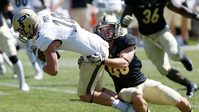Cameron Posey of the Gold team is brought down by Race Johnson of the Black after a pass reception during the Purdue spring football game Saturday, April 16, 2016, at Ross-Ade Stadium. The Black team defeated the Gold 23-17.