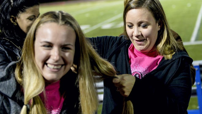 Chelsea Lutz has her hair cut by Raquel Sides in this photo taken Oct. 30, 2015, at Cedar Crest's Earl Boltz Stadium. Thirty students and staff donated their hair to Pantene Beautiful Lengths, which make wigs for cancer victims.