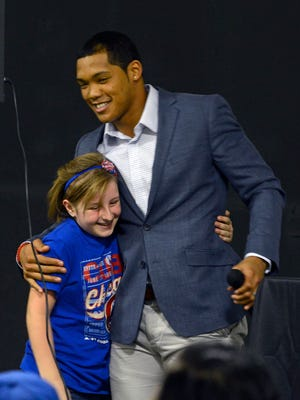 Moriah Ingram,10, gets a hug from Addison Russell of the Chicago Cubs Sunday during a meet and greet at Unlimited raining Academy.