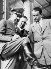 In this file photo dated Feb. 19, 1937, German Chancellor Adolf Hitler, left, discusses plans for building a convention hall at Nuremberg with Lord Mayor Willy Liebel, centre, and Prof. Albert Speer, right, at Nuremberg, Germany.