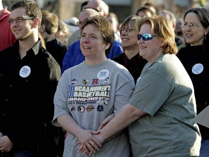 Stacey Bonnett, center left, and Kate Dahlke, center right, both of East Des Moines,  listened to a speaker as they attended  a rally held by One IOWA, the state's largest lesbian, gay, bisexual and transgender  ( LGBT ) advoacy group, on Friday afternoon, April 3rd.    On Friday morning, the Iowa Supreme Court made a unanimous ruling that gay and lesbian couples must be allowed to marry in Iowa.  The rally was held at Western Gateway Park in downtown Des Moines.