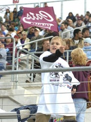 Andy Johnson, 7, waves a sprit flag as the Calallen Wildcats take the field for the Class 4A Division II state championship game against Lewisville Hebron on December 17, 2005 at the Round Rock ISD Stadium.