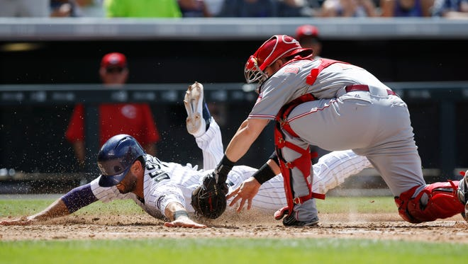 Colorado Rockies' Daniel Descalso, left, dives safely into home plate to score on a bunt by Kyle Kendrick as Cincinnati Reds catcher Tucker Barnhart applies a late tag in the third inning of a baseball game Sunday, July 26, 2015, in Denver.