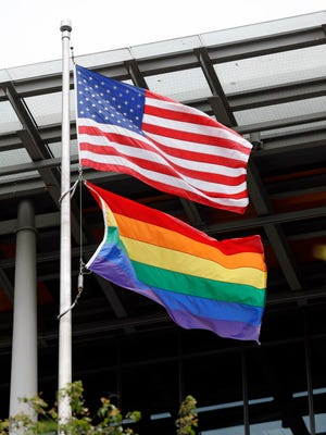 A gay pride flag next to the United States' flag at Seattle's City Hall.