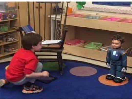 Benjamin Blatt, 7, interacts with Milo, a facially