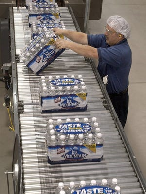 Ice Mountain employee Dan Decator of Hersey checks packages of bottled water coming off the line in the Mecosta County water bottling plant in Stanwood, Mich., Feb. 16, 2003.