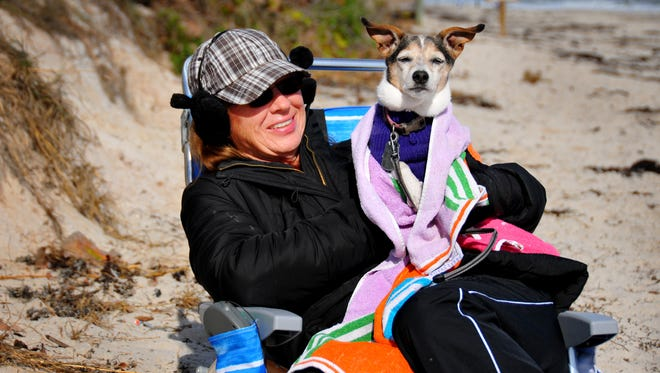 Yuvonia Mardis and her dog Zip bundled up to stay warm during a December 2016 wintry blast at the Canova Beach Park dog beach near Indian Harbour Beach.