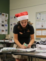 Students from Oaks Christian School wrapped gifts to deliver to families who have a child with cancer.