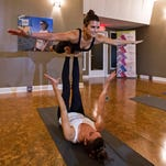 "Danica Patrick, top, does acrobatic yoga with Morgan DeYoung, aka ""The Southern Yogi,"" during 2016 Daytona Speedweeks."