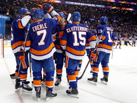 New York Islanders center Jordan Eberle is congratulated by teammates after scoring the game winning goal in overtime of an NHL hockey game against the Los Angeles Kings, Saturday, Dec. 16, 2017, in New York. The Islanders won 4-3 in overtime. (AP Photo/Adam Hunger)