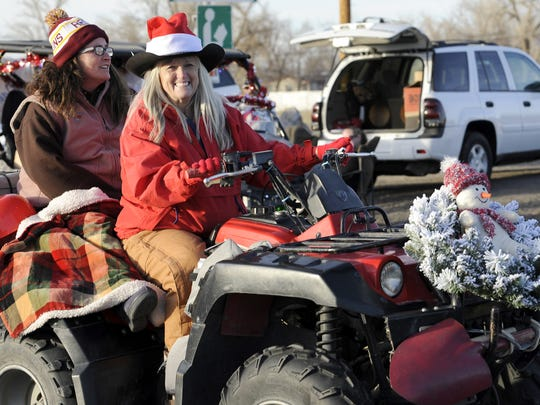 Danie Walsh and her daughter, Lory Walsh, ride an off-road vehicle in the parade.