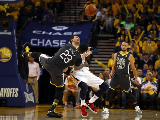 Golden State Warriors' Draymond Green (23) collides with New Orleans Pelicans' Nikola Mirotic as Stephen Curry, right, watches in the second half in Game 2 of a second-round NBA basketball playoff series Tuesday, May 1, 2018, in Oakland, Calif. Golden State won 121-116.