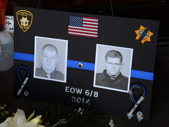 A poster with the images of the police officers that were killed is shown at a memorial at CiCi's Pizza during a vigil outside the restaurant on June 9, 2014 in Las Vegas, Nevada.