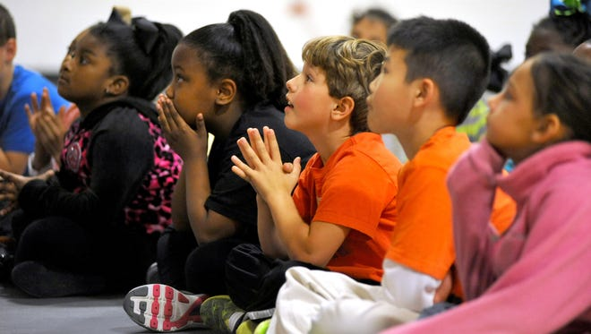 Clinton Northside Elementary School students listen to a persentation during a physical education class at the school Thursday.