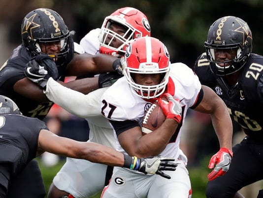 FILE - In this Oct. 7, 2017, file photo, Georgia tailback Nick Chubb (27) gets past Vanderbilt safety Arnold Tarpley III (2) during the first half of an NCAA college football game in Nashville, Tenn. Chubb is the leader of an unusually deep collection of tailbacks that has powered No. 2 Georgia to a chance for its best start in 35 years when it faces South Carolina on Saturday. A win would give Georgia a 9-0 record for the first time since 1982. Georgia may play as many as five tailbacks against the Gamecocks. (AP Photo/Mark Humphrey, File)