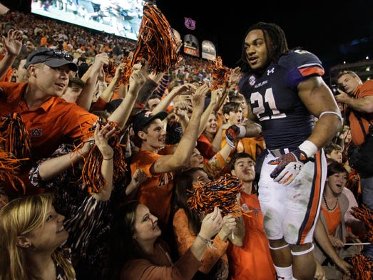 Auburn Tigers running back Tre Mason (21) celebrates with fans after beating the Georgia Bulldogs 43-38 at Jordan Hare Stadium.