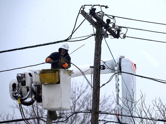 Work on power lines continues in Irondequoit as snow moved into area Tuesday morning.