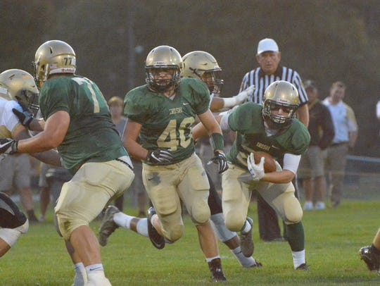 York Catholic's Andrew Snelbaker runs for a gain against