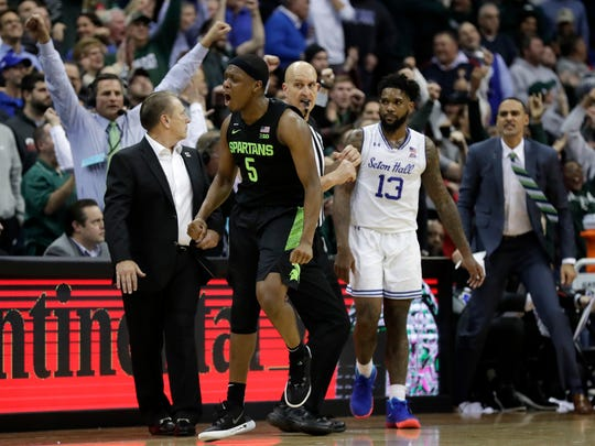 Michigan State guard Cassius Winston (5) reacts after making a three-point basket in front of Seton Hall guard Myles Powell (13) during the second half of an NCAA college basketball game Thursday, Nov. 14, 2019, in Newark, N.J. (AP Photo/Adam Hunger)