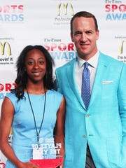 Peyton Manning poses with Female City Basketball Player