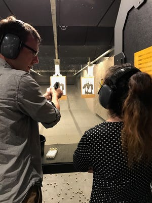 Naples Daily News reporter and self-proclaimed gun expert Thaddeus Mast shows reporter Ashley Collins the basics of handling a pistol.