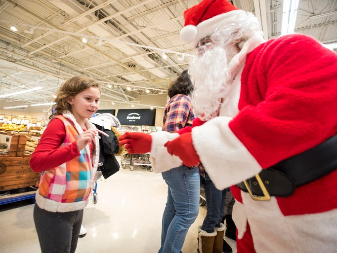 Santa Claus hands a candy cane to Summer Johnson, 7,