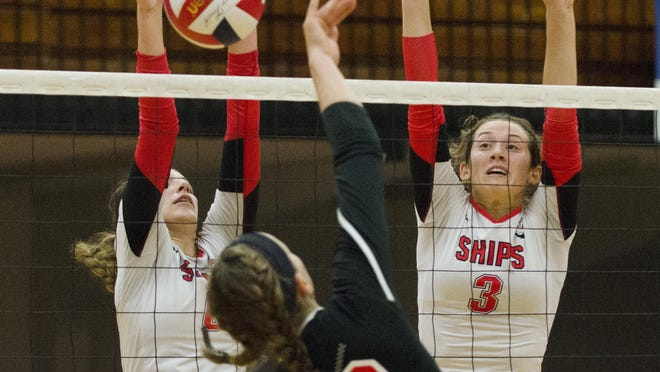 Manitowoc Lincoln's Rayna Figueroa, left, and Christina Maser successfully block a spike from Sheboygan South's Ashley Weimann during the first game of a match against Sheboygan South at the JFK Fieldhouse Thursday.