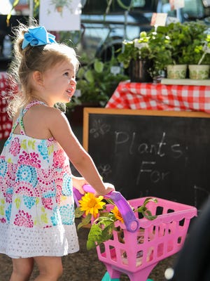 Kinsley Miles, 3, pushes a cart while at the Concho Valley Farmers Market Saturday, May 13, at 609 S. Oakes St. in San Angelo.