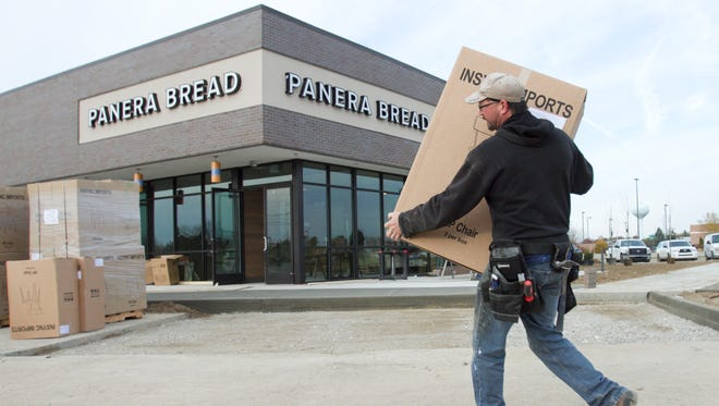 Tony Moore of Pearce Building Co. carries chairs into the soon-to-open Panera Bread in Genoa Township.